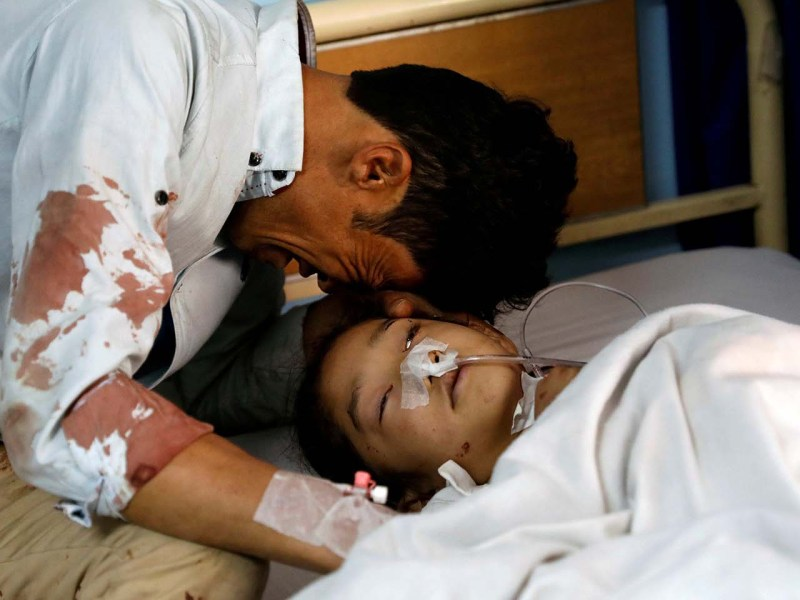A man cries beside an injured girl at a hospital after a suicide bomb attack in Kabul near a school where voters were registering for ID cards so they can vote in the upcoming election. Photo: Reuters/ Mohammad Ismail