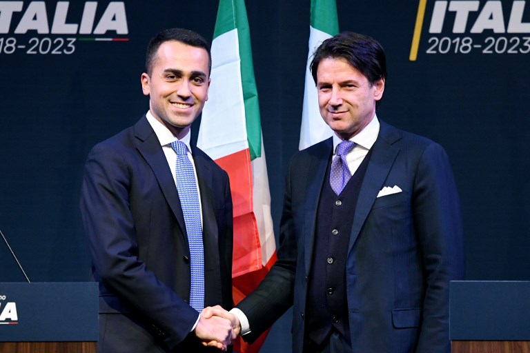 Italy's populist Five Star Movement leader Luigi Di Maio (L), shakes hands with Italian lawyer Giuseppe Conte, a possible choice to lead a coalition government.