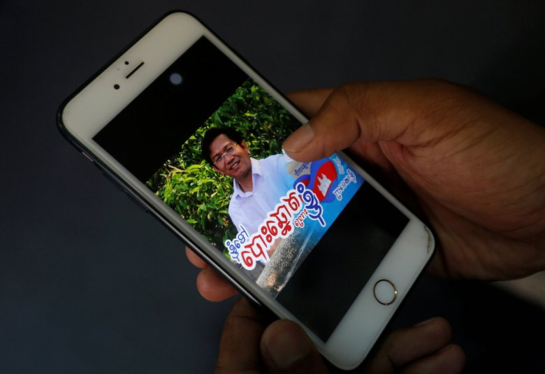 "A man looks at a Facebook profile photo of Huy Vannak, undersecretary of state at the Ministry of Interior of Cambodia, with words that read ''I go to vote because I'm a Khmer nationalist"" in Phnom Penh, Cambodia, May 17, 2018. REUTERS/Samrang Pring"
