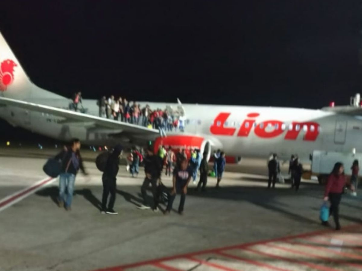Passengers jump from the wing of the plane after getting out through the emergency exits after a man falsely claimed there was a bomb on board. Photo: Twitter/@greendulu