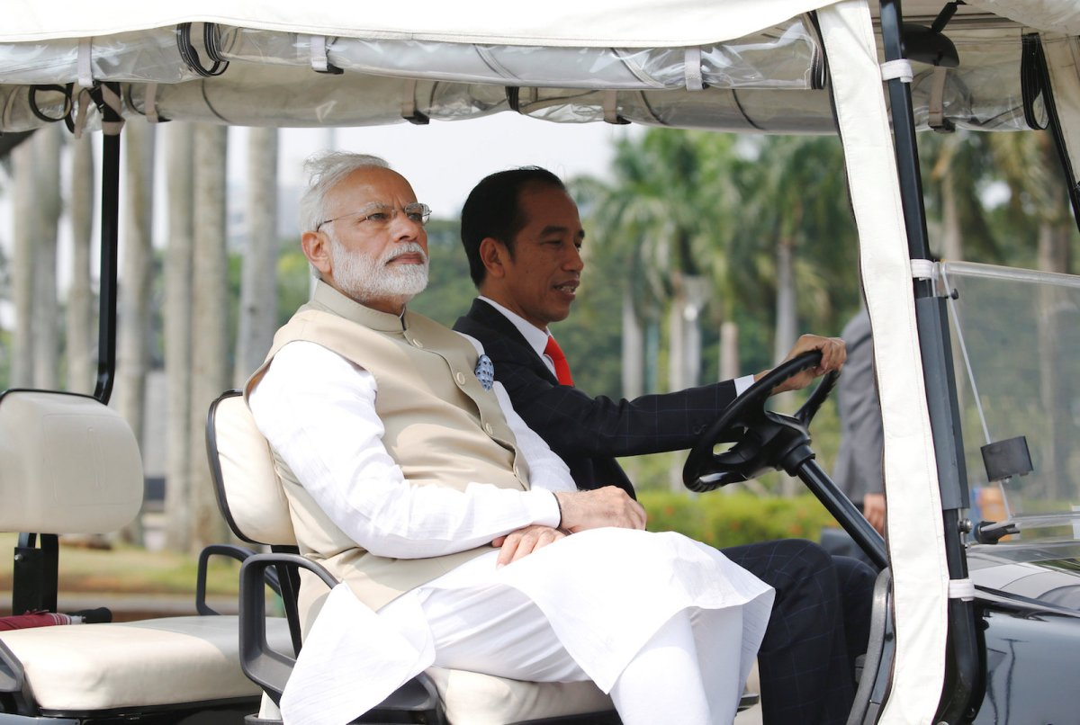 Indian Prime Minister Narendra Modi sits as Indonesia President Joko Widodo drives a golf cart at the National Monument in Jakarta on May 30, 2018. Photo: Reuters / Beawiharta