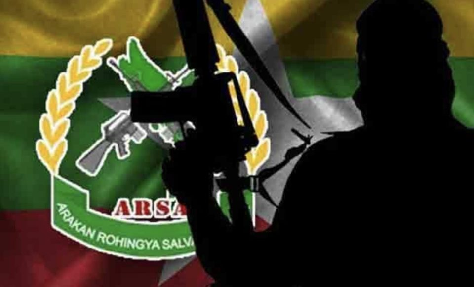 A silhouetted Arakan Rohingya Salvation Army fighter against the rebel group's flag. Photo: Youtube