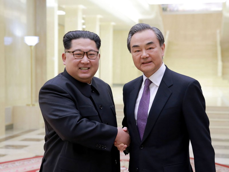 North Korea's leader Kim Jong Un (L) shaking hands with China's Foreign Minister Wang Yi (R) during their meeting at an undisclosed location in North Korea on May 3, 2018. Photo: AFP via KCNA