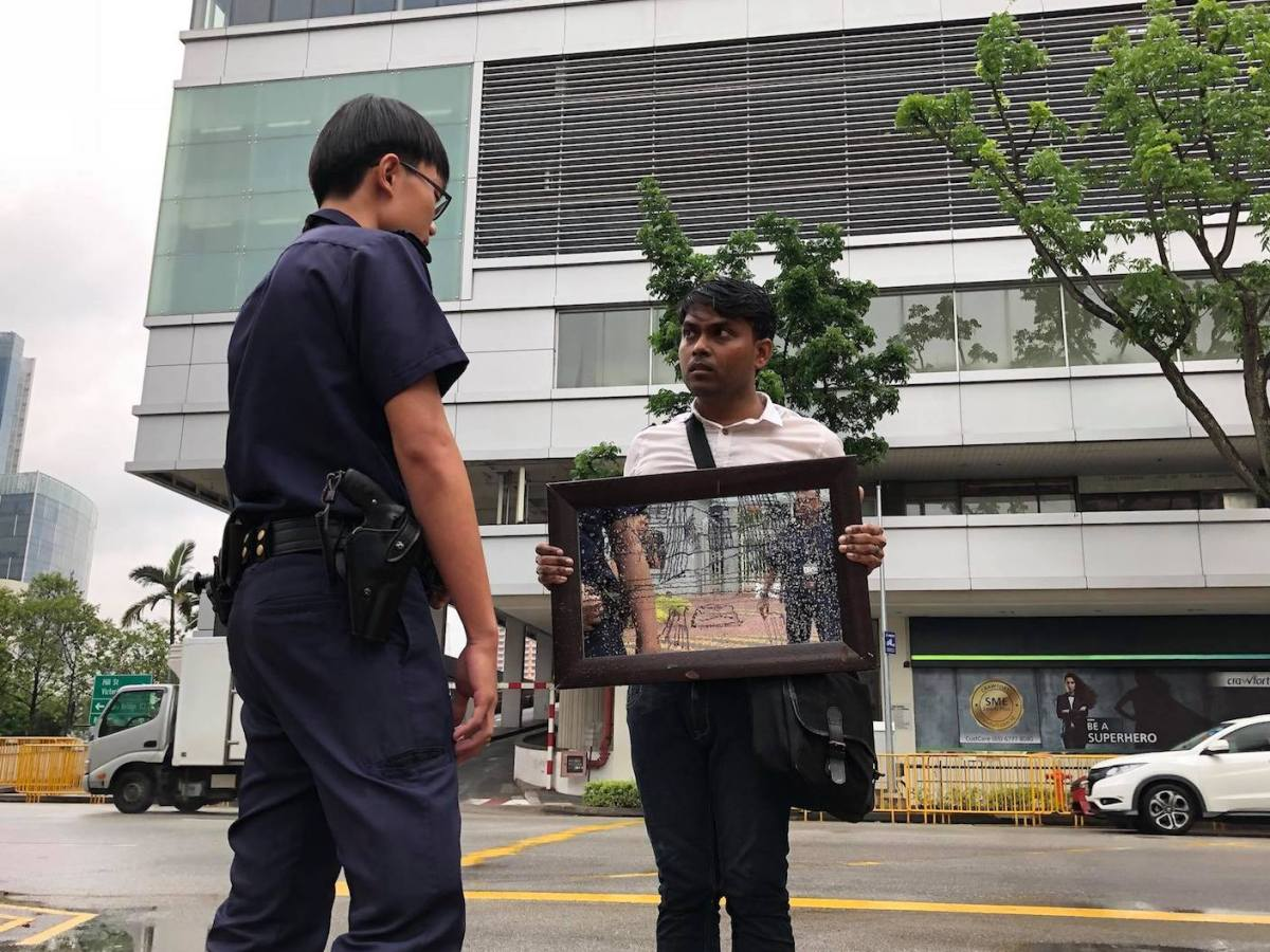 Singaporean artist Seelann Palay is confronted by police while holding a solo silent protest against the repression of a former parliamentarian, October 1, 2017, Singapore. Photo: Courtesy of The Online Citizen