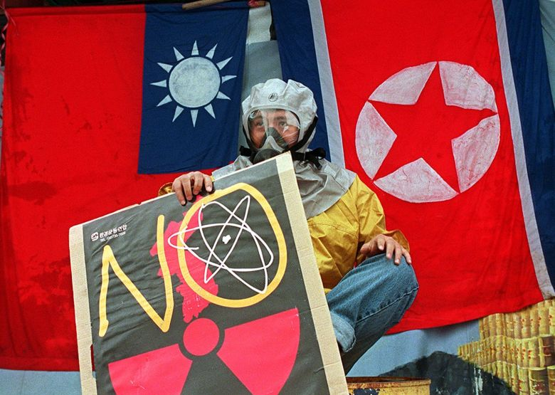 A gas-masked South Korean environmental activist holds an anti-nuclear picket in front of Taiwanese and North Korean flags placed by the protestors in Seoul 16 July. The demonstration was to protest against Taiwan's plan to ship nuclear waste to North Korea for disposal. AFP  PHOTO / AFP PHOTO / CHOO YOUN-KONG