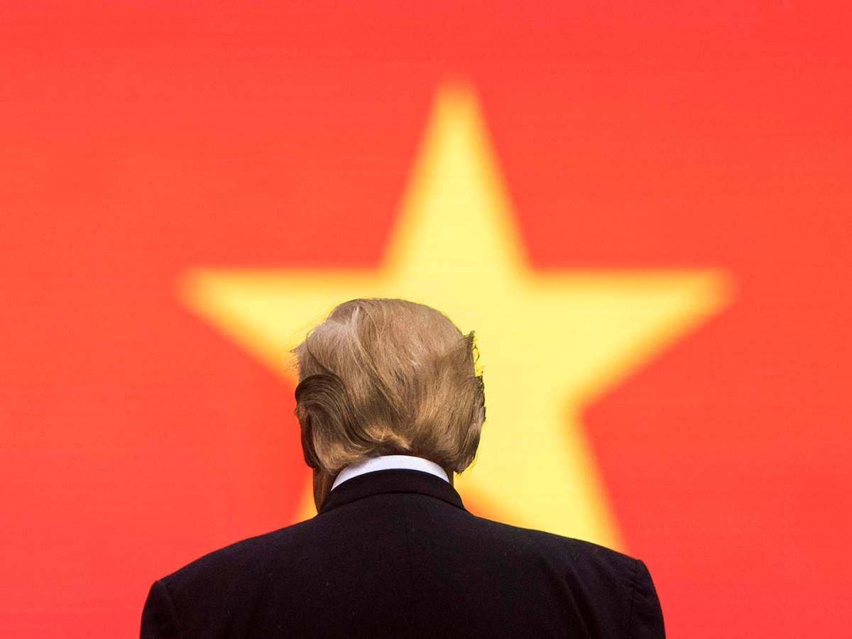 US President Donald Trump stands before a Vietnamese flag during an arrival ceremony in Hanoi, November 12, 2017. Photo: AFP/Jim Watson