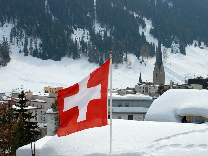 Swiss flag in Davos town with church and mountains in the background. Davos is a ski resort and location of the annual World Economic Forum.Please see more flag pictures: Photo: iStock