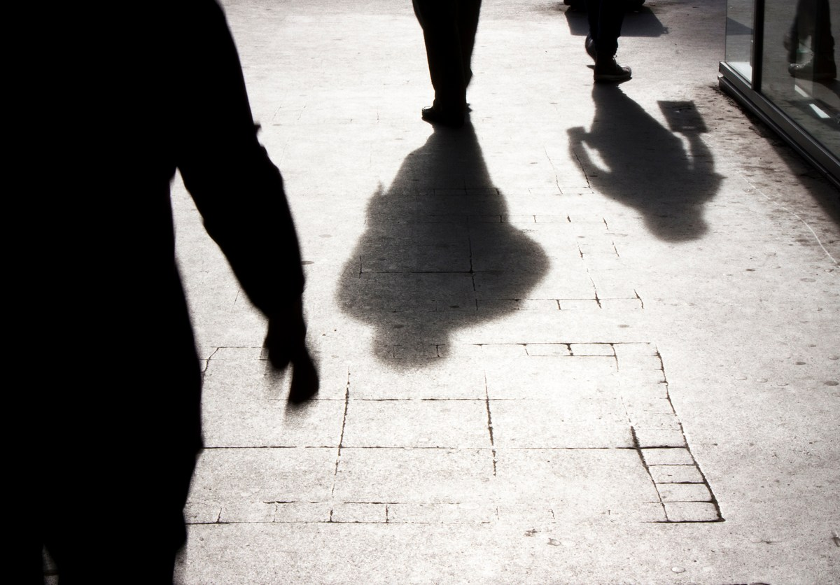 Blurry silhouettes and shadows of people walking on the city sidewalk.Photo: iStock
