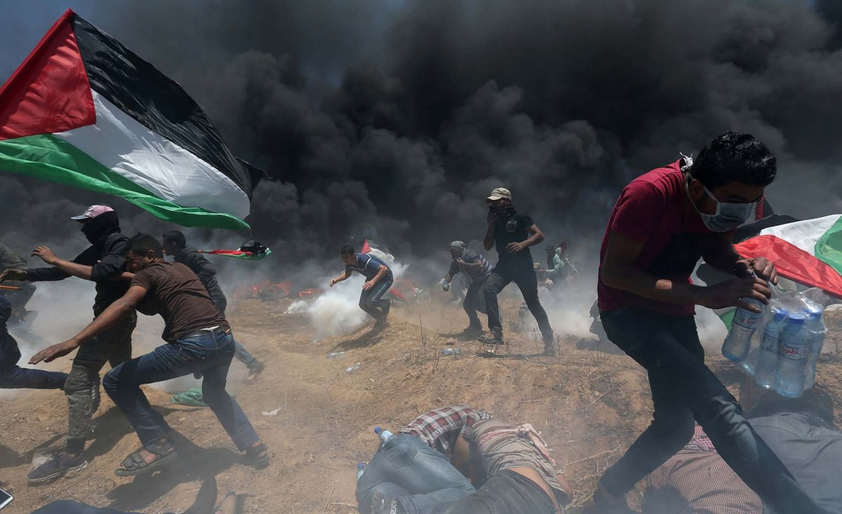 Palestinian demonstrators run for cover from Israeli gunfire and tear gas during a protest against US embassy move to Jerusalem at the Israel-Gaza border in the southern Gaza Strip on May 14, 2018.  Photo: Reuter/Ibraheem Abu Mustafa