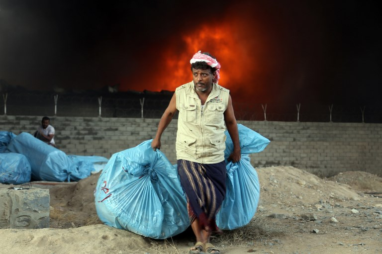 A Yemeni worker evacuates food bags as fire engulfs the United Nations' World Food Programme's warehouse in the coastal town of Hodeida in March. Photo: AFP/Abdo Hyder