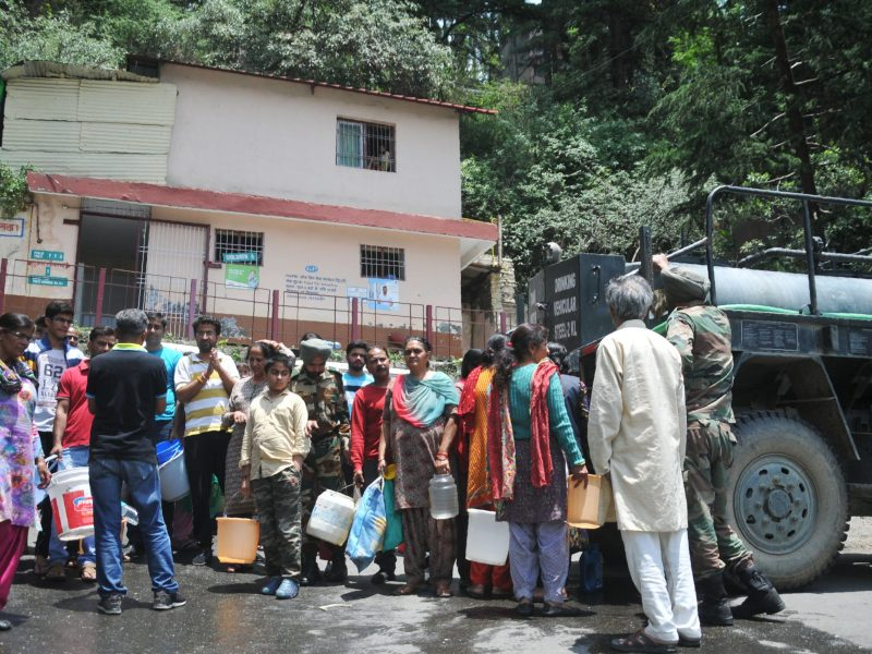 Indian residents gather to collect drinking water in buckets from an Indian Army water tanker as the city faces water shortage in Shimla, in the northern state of Himachal Pradesh on June 2, 2018. Helicopters doused forest fires raging near the drought-stricken Indian resort of Shimla on May 1 ore police were deployed to guard water tankers in the historic Himalayan town. Shimla's water shortage has been worsening for years but reached crisis point when supplies ran out last month, just as the population of 175,000 started growing by up to 100,000 for the summer season. / AFP PHOTO / -