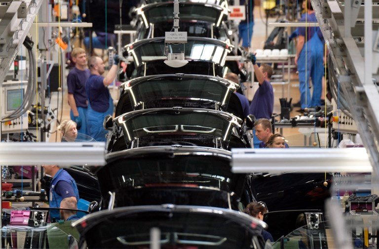 BMW staff working on the production of the electric car i3. Photo: dpa via AFP/Sebastian Willnow