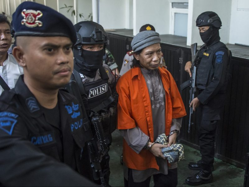 Armed police escort Aman Abdurrahman, leader of militant outfit Jamaah Ansharut Daulah, a group linked to the Islamic State (ISIS), to a court hearing in Jakarta on May 18, 2018.Photo: AFP / Bay Ismoyo