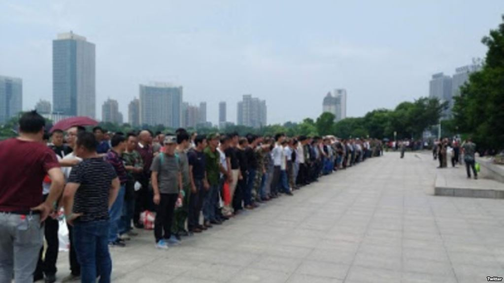 Thousands of disgruntled former soldiers gather outside the government compound in Zhenjiang in east China. Photo: Twitter