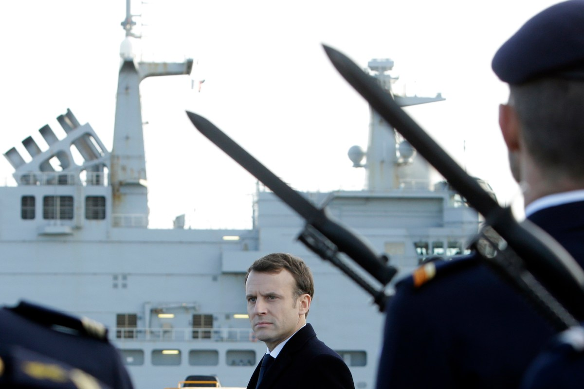 """French President Emmanuel Macron reviews an honor guard of the French Navy aboard the French Mistral Class assault ship and helicopter carrier """"Dixmude"""", January 19, 2018. Photo: AFP/ Claude Paris"""