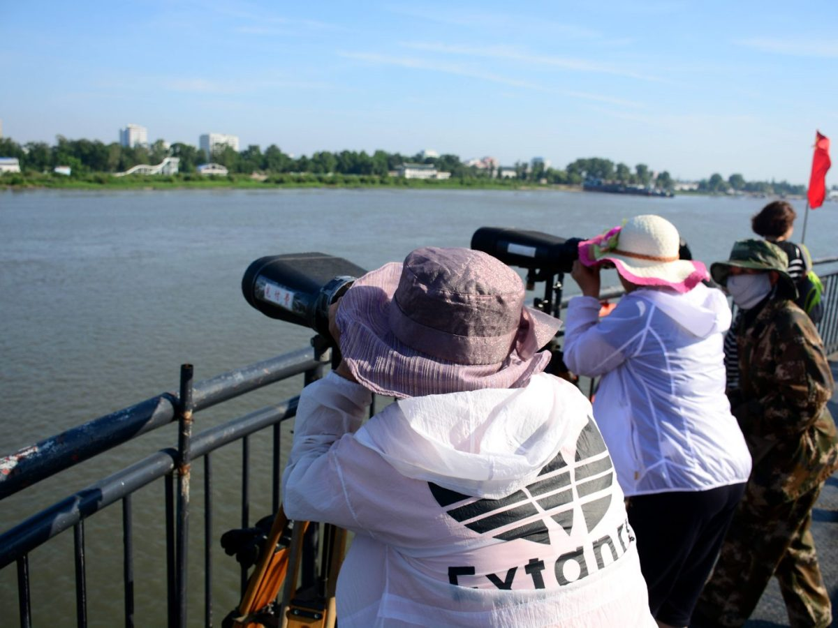 Tourists look into North Korea from across the border in China. Change is in the air, but the question is what will change? Photo: AFP
