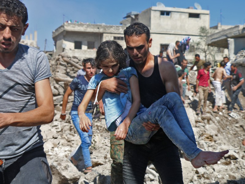 A man carries a child rescued from rubble after Syrian regime and Russian air strikes in the rebel-held town of Nawa, 30km north of Daraa in southern Syria on June 26. Syria's army launched an assault on Daraa on Tuesday, after a week of bombardment on the nearby countryside caused mass displacement. Photo: AFP/ Ahmad al-Msalam
