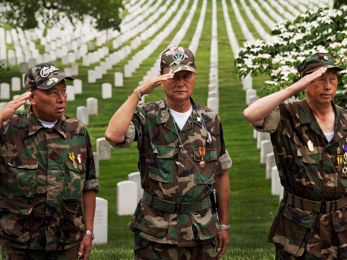 Members of the Lao Veterans of America salute as the colors are presented by US Honor Guard during a memorial service and wreath laying ceremony for Major General Vang Pao, May 13, 2011. Photo: AFP/ Paul J. Richards