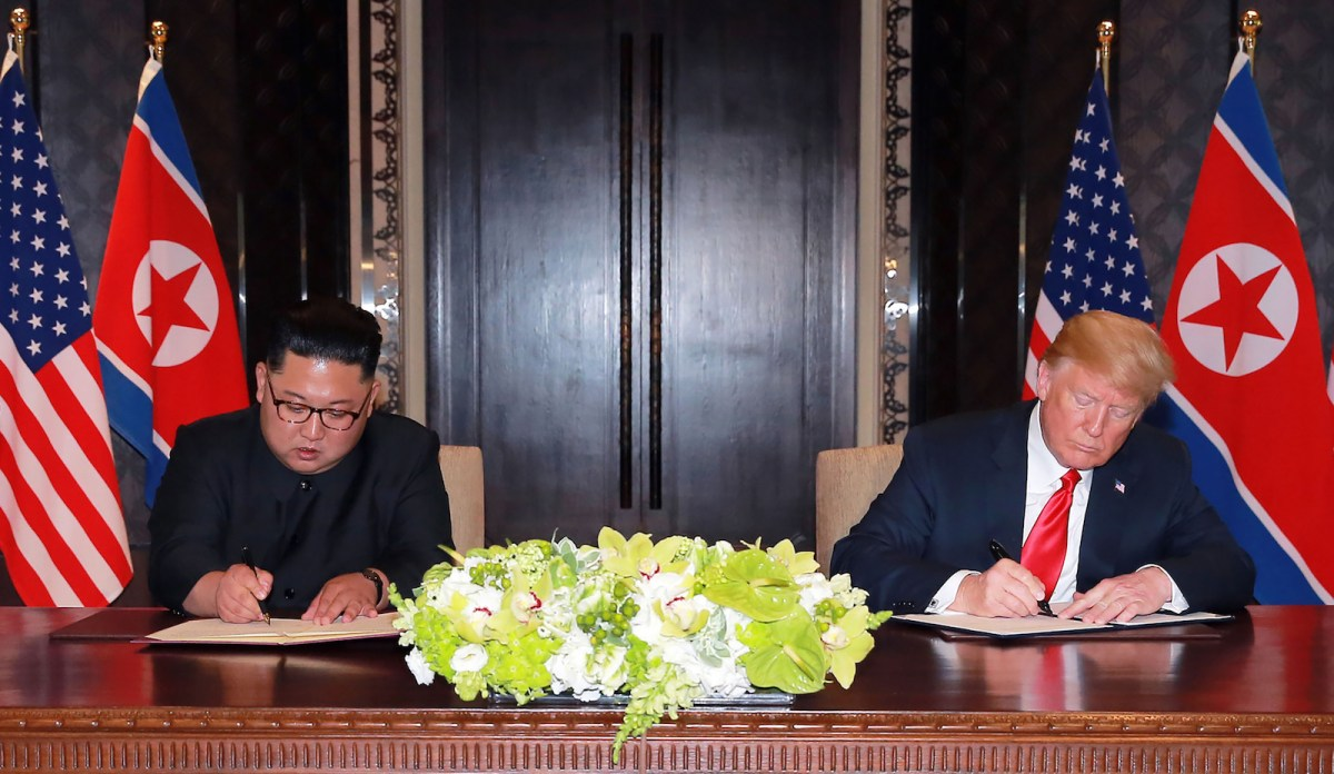 US President Donald Trump (R) and North Korea's leader Kim Jong Un (L) sign documents at a signing ceremony during their historic US-North Korea summit, at the Capella Hotel on Sentosa island in Singapore. Photo: AFP via KCNA/KNS