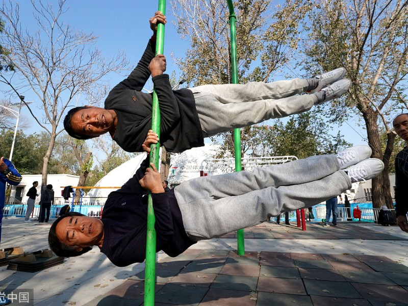 Two senior residents in China's Tianjin are seen in a local park doing morning exercises. Photo: Xinhua via VCG