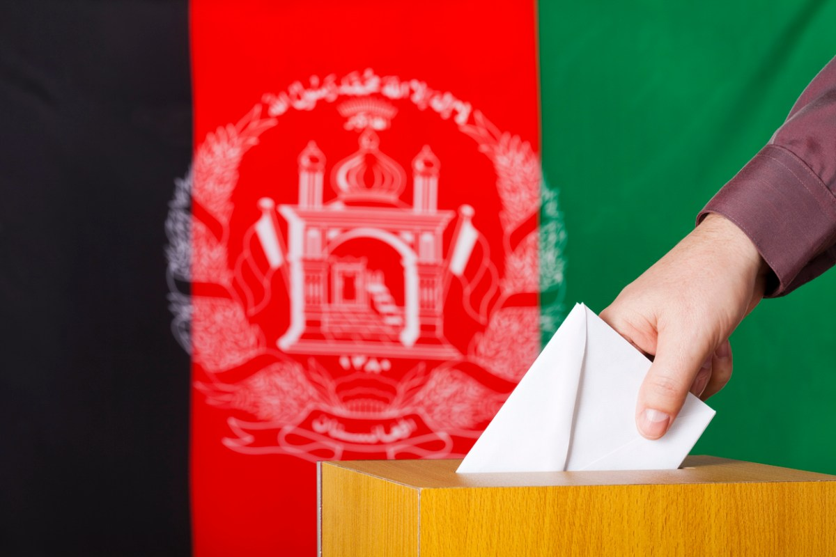 Male hand inserting a ballot to a ballot box. Flag of Afghanistan in the background. Photo: iStock