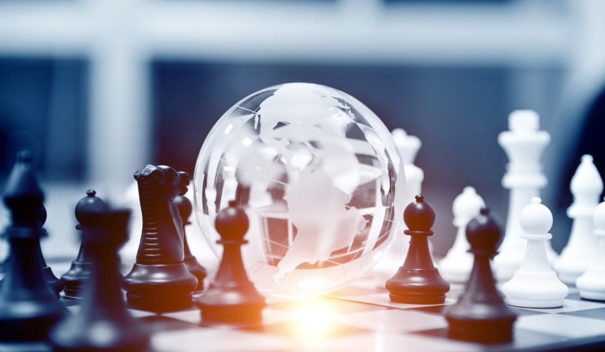 Crystal globe and chess pieces on chessboard. Photo: iStock