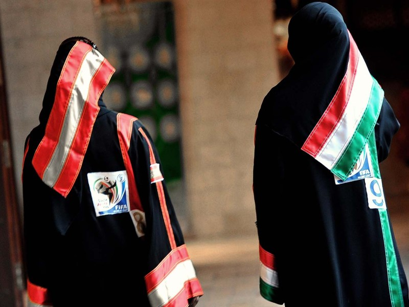Saudi women, wearing their World Cup abayas, or dresses, with the colors of the flags of countries taking part in the World Cup 2010, walk through a shopping mall in Jeddah on June 18. Photo: AFP/Amer Hilabi