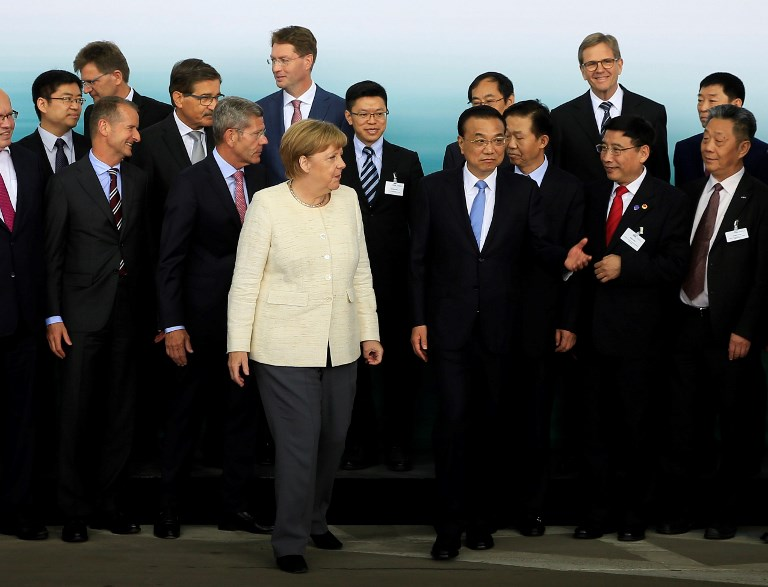 German Chancellor Angela Merkel and Chinese Premier Li Keqiang pose for a photo with officials as they attend a presentation on autonomous driving. Photo: AFP