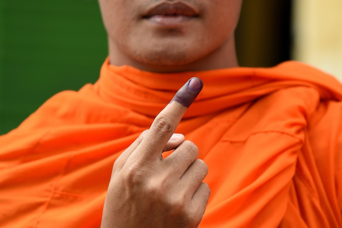 A Cambodian Buddhist monk shows his inked finger after casting his vote during Cambodia's general election in Phnom Penh on July 29, 2018. Photo: AFP/Manan Vatsyayana