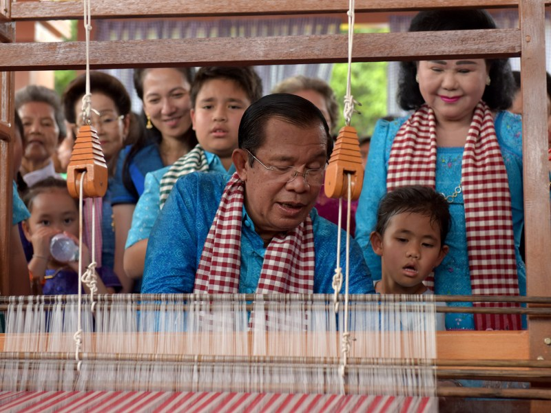 Cambodia's Prime Minister Hun Sen (C) weaves as his wife Bun Rany (top R) looks on during an opening ceremony for the Khmer New Year at Bayon temple at the Angkor complex in Siem Reap province on April 13, 2018. Photo: AFP/Tang Chhin Sothy