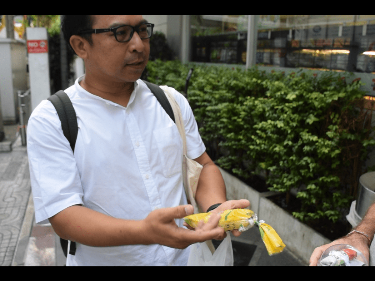 Greenpeace country director Tara Buakamsri holds a banana sold in a plastic bag by 7-Eleven, which he said was an example of the excessive use of plastic in Thai society. Photo: Rajat Sethi