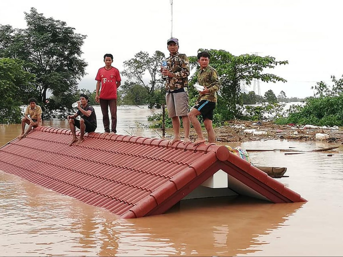 Residents on rooftops surrounded by floodwaters in Attapeu province after a dam collapsed on July 23.Photo: AFP/Attapeu Today