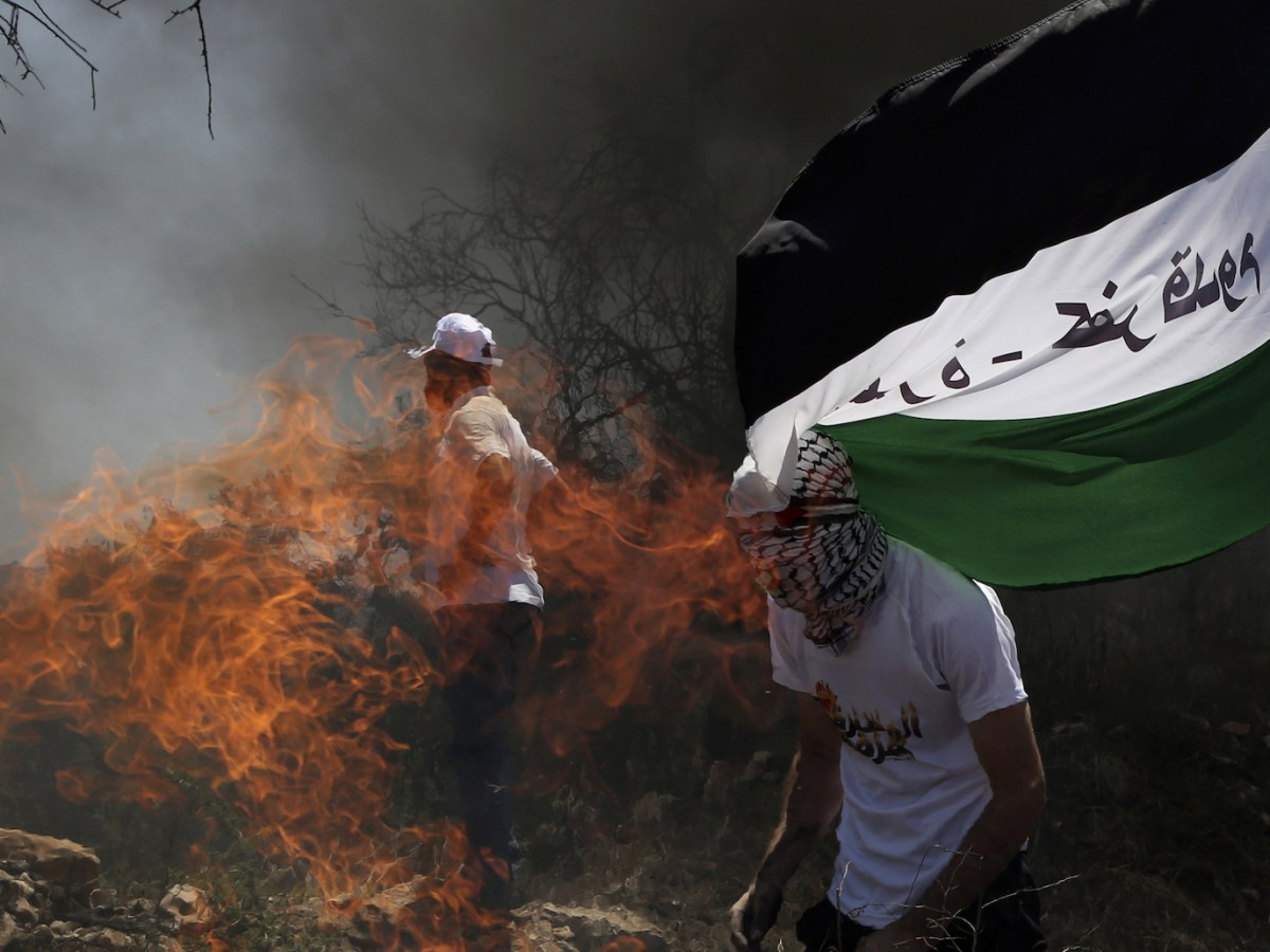 Palestinian protesters burn tyres during a weekly demonstration against the expropriation of Palestinian land by Israel in the village of Kfar Qaddum, near Nablus in the occupied West Bank, on July 6, 2018. Photo: AFP/ Jaafar Ashtiyeh