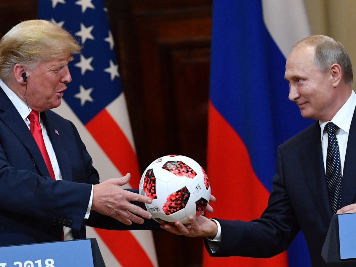 Russian President Vladimir Putin offers a ball from the 2018 World Cup to US President Donald Trump after a meeting in Helsinki in July. Photo: AFP