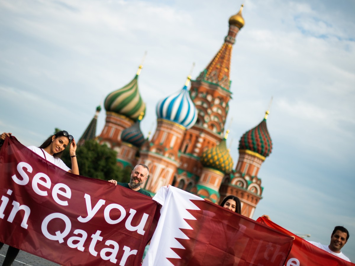 A group of fans in Moscow's Red Square display a banner reading 'See you in Qatar' in reference to the 2022 World Cup. Photo: AFP / Jewel Samad