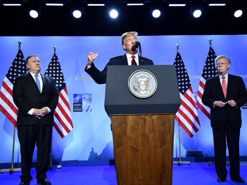 US President Donald Trump, center, is seen with US Secretary of State Mike Pompeo, left, and US National Security Advisor John Bolton as he talks to the press at the North Atlantic Treaty Organization (NATO) summit in Brussels on July 12. Photo: AFP/ Brendan Smialowski