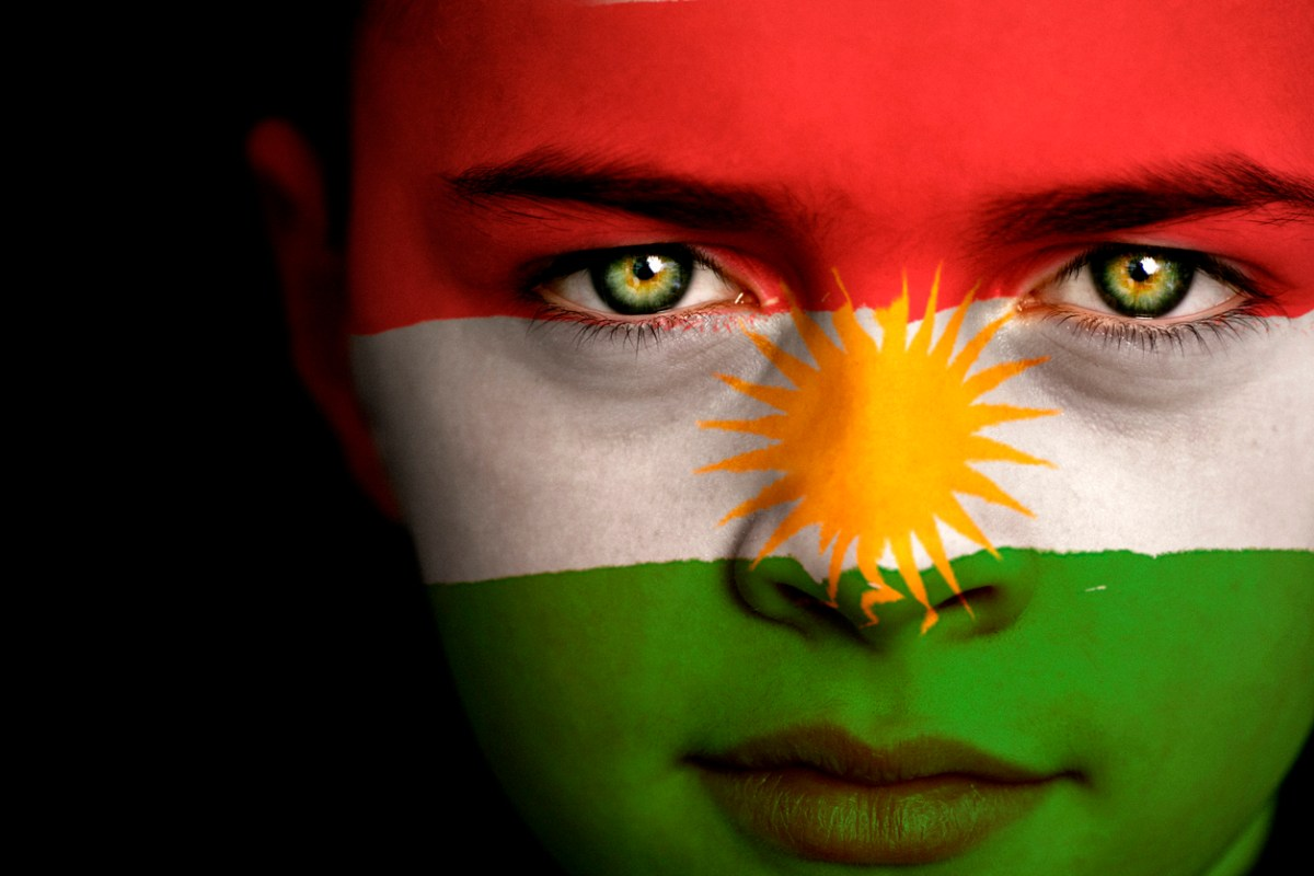 Portrait of a boy with the flag of Kurdistan painted on his face. Photo: iStock