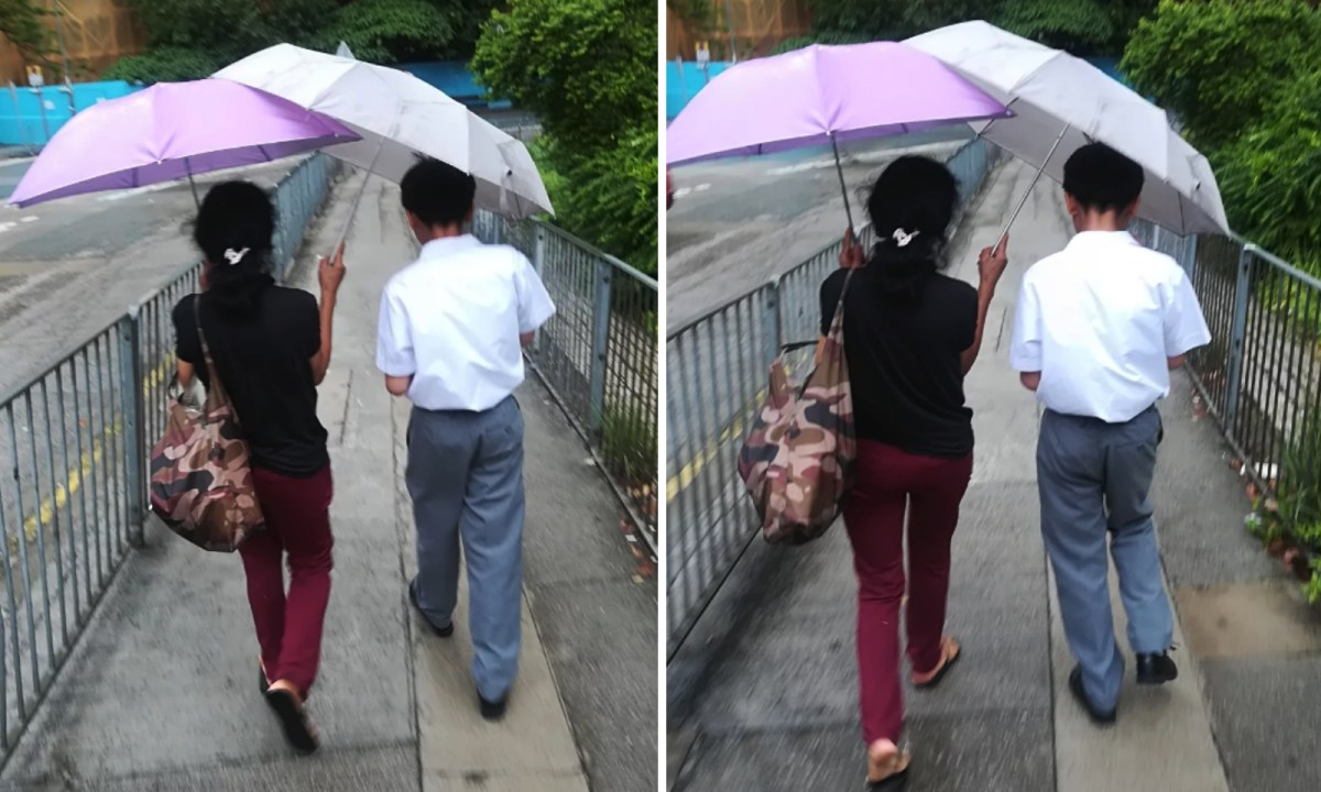 A domestic worker holds an umbrella for a boy. Photo: Hong Kong Discuss Forum
