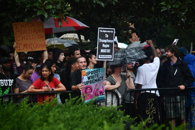Demonstrators opposed to a far-right rally hold signs  opposite the White House on August 12. Photo: AFP