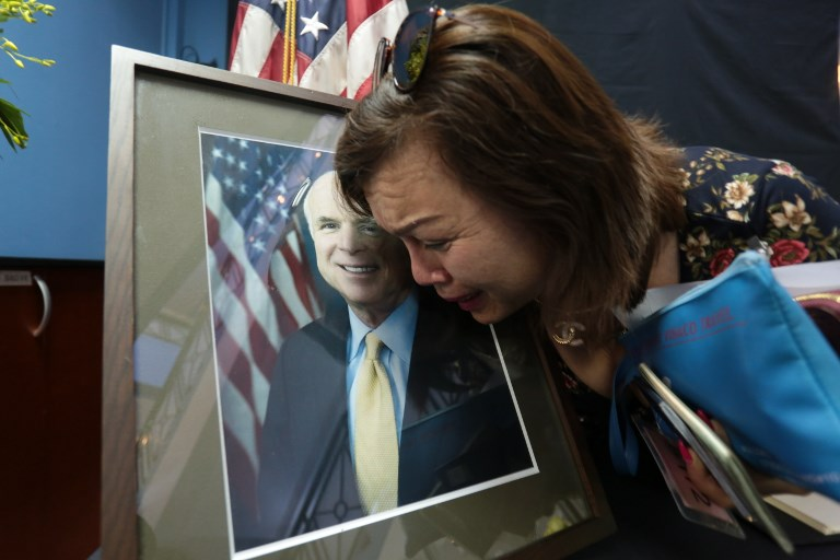 Mai Tran, an American of Vietnamese descent grieves over the portrait of the late US Senator John McCain during a memorial tribute at the US embassy in Hanoi on August 27, 2018. John McCain, a war hero and towering figure in US politics known for reaching across the aisle in an increasingly divided nation, died on August 25 at the age of 81 following a battle with brain cancer. Photo: AFP