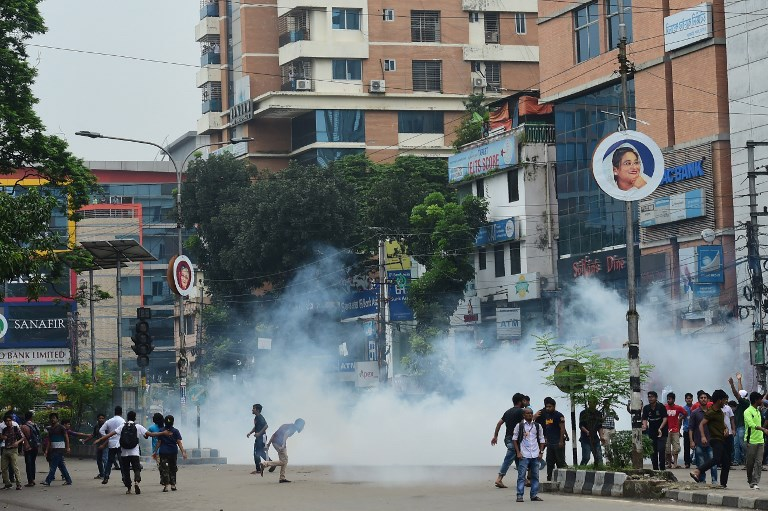 Bangladeshi students stand on a road amid teargas during clashes with police in the protest in Dhaka on August 5, 2018, after the death of two students in a road accident. Photo: AFP / Munir Uz Zaman