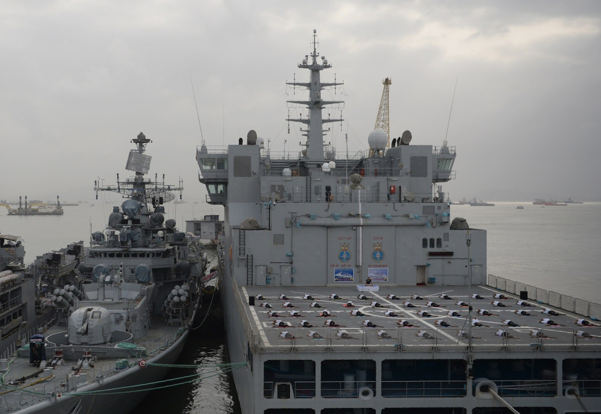 Indian military personnel take part in a yoga session on an Indian Navy ship anchored in Mumbai harbour on June 21, 2018. Photo: AFP / Punit Paranjpe