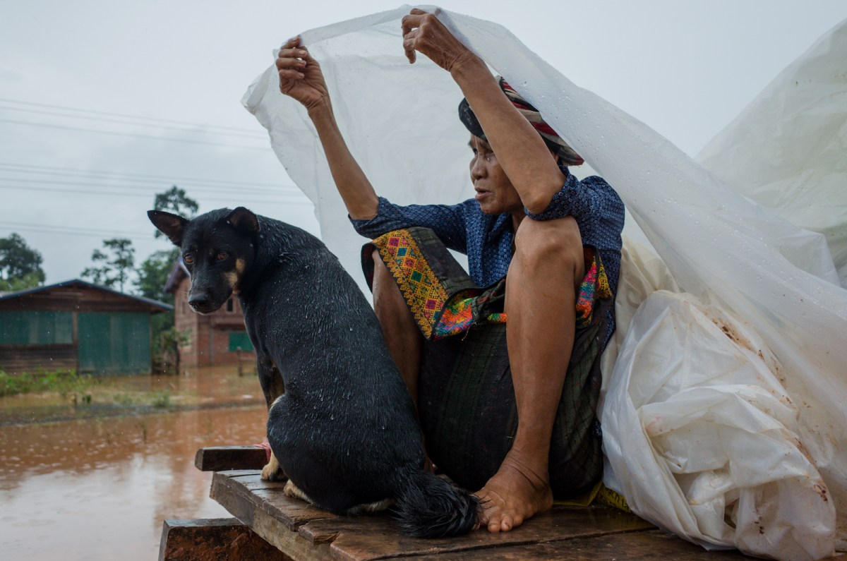 A woman with a dog ride on a vehicle carrying belongings in the flooded area in Sanamxai, Attapeu province, on July 26, 2018. Photo: AFP/Kao Nguyen