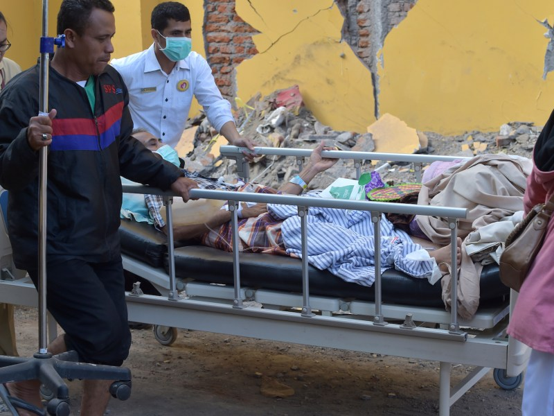 An injured quake victim is wheeled past a damaged wall in Mataram on the Indonesian island of Lombok on August 6, 2018, the morning after a 6.9 magnitude stuck the island. Photo: AFP / Adek Berry