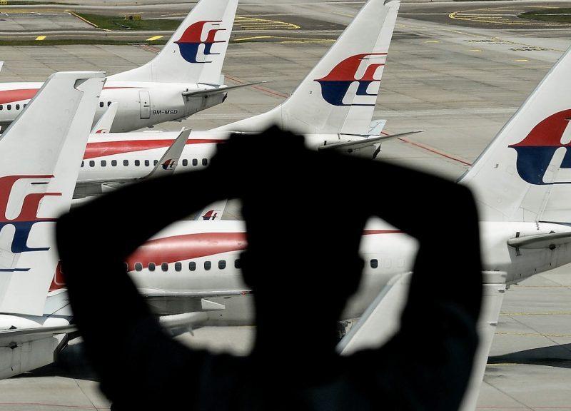 2016年2月25日,一名男子看著馬來西亞航空公司的飛機停在雪邦的吉隆坡國際機場停機坪上。相片:AFP / Manan Vatsyayana