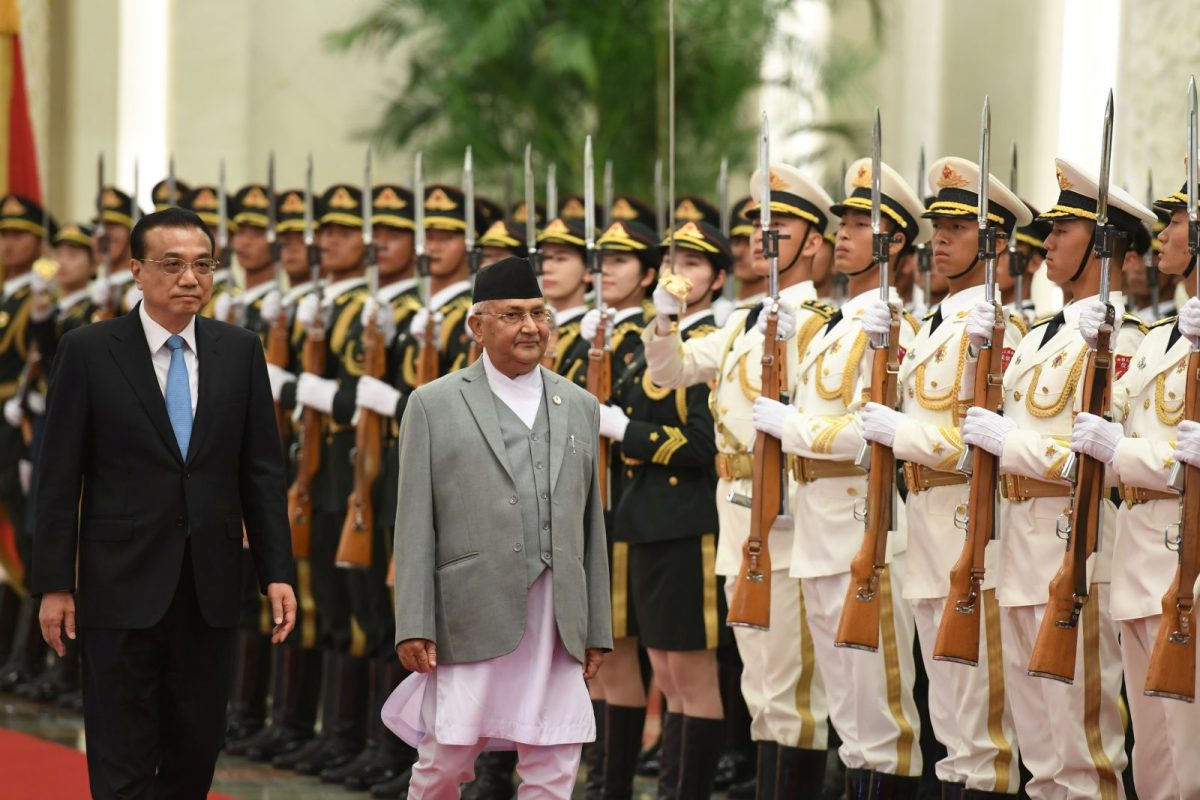 Nepalese Prime Minister K P Sharma Oli (center) and Chinese Premier Li Keqiang review a military honor guard during a welcome ceremony at the Great Hall of the People in Beijing on June 21, 2018. Photo: AFP / Greg Baker