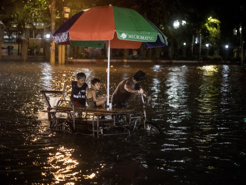 A rickshaw driver and children on a flooded street due to a heavy downpour brought about by tropical storm Yagi, August 11, 2018. Photo: AFP/Noel Celis