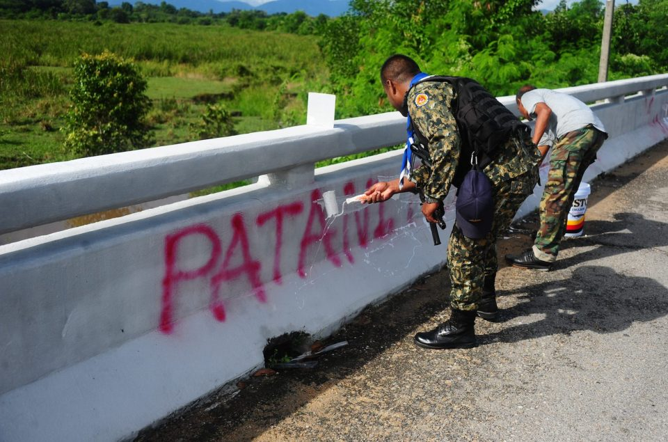 Thai soldiers paint over separatist messages left on a bridge by suspected militants the night before in the Yingo district in Thailand's restive southern province of Narathiwat on November 3, 2016.Three people were shot dead in a night of co-ordinated violence across Thailand's rebellious 'Deep South', in attacks apparently timed with a visit by the new minister for the restive Muslim-majority region. The attacks began late on November 2 and rippled out over a wide area in the following hours with shootings, arson and bombings as well as the unfurling of banners decrying the Thai state, which colonised the region more than a century ago. / AFP PHOTO / MADAREE TOHLALA