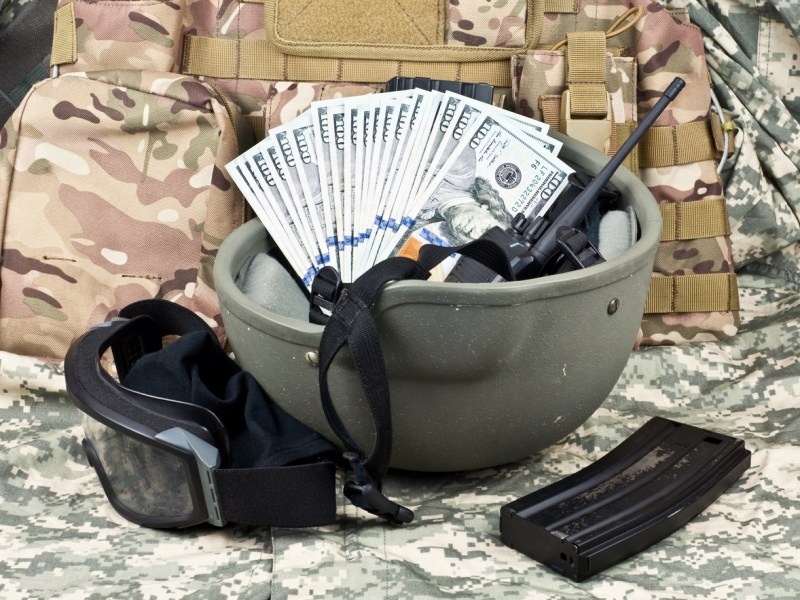 dollar bills against the background of military equipment. Photo: iStock