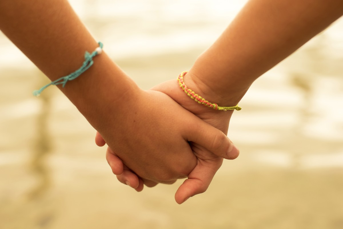 Close up of two children holding hands on the beach sand, summertime friendship concept. Photo: iStock